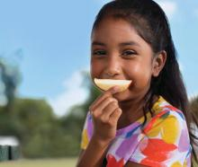 A young girl holds an apple slice over her mouth like a smile