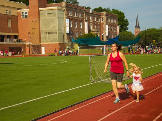 Mother and daughter job around a track with the YMCA building in the background.